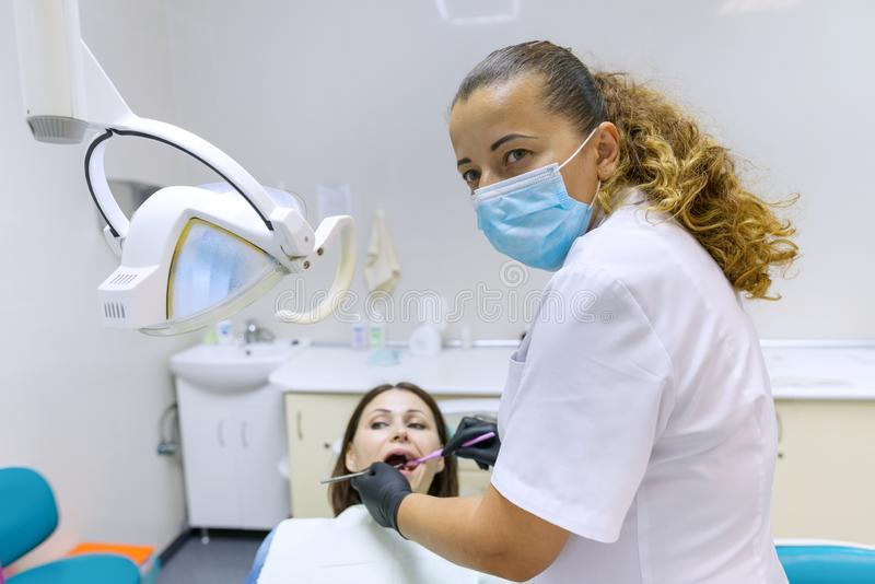 Portret van positieve rijpe vrouwelijke tandarts die patiënt als tandvoorzitter behandelen stock fotografie