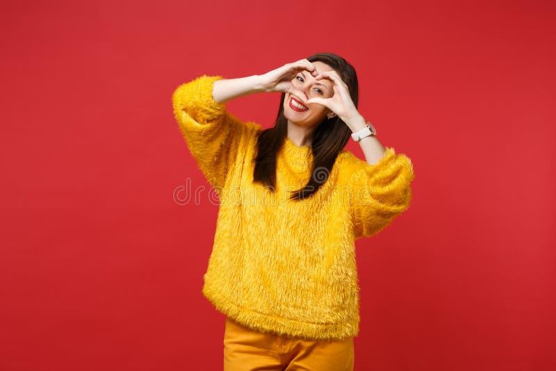 Portret van prettige jonge vrouw in gele bontsweater die vormhart met handen tonen die op heldere rode muur wordt geïsoleerd royalty-vrije stock fotografie