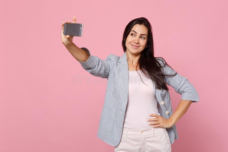 Portret van prettige vrij jonge vrouw in gestreept jasje die selfie schot op mobiele die telefoon doen op roze pastelkleur wordt  stock fotografie