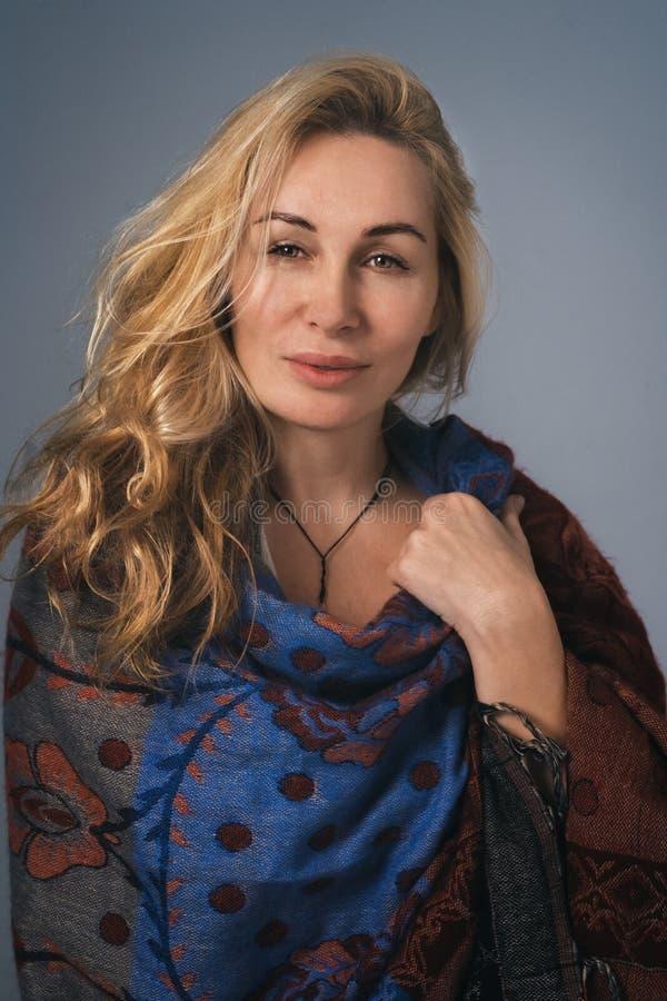 Portret van prettige vrouw die in sjaal wordt verpakt stock foto