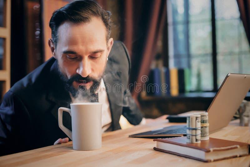Portret van rijpe mensenzitting bij zijn bureau in het bureau stock fotografie