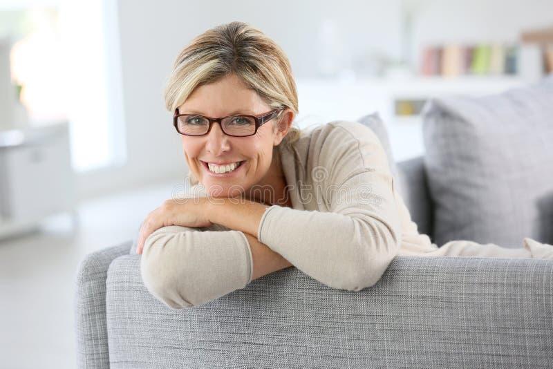 Portret van rijpe vrouw bij bank het ontspannen royalty-vrije stock foto