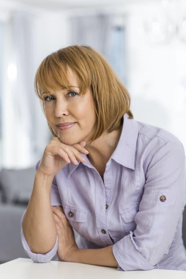 Portret van rijpe vrouw met hand op kinzitting bij lijst binnenshuis royalty-vrije stock foto's