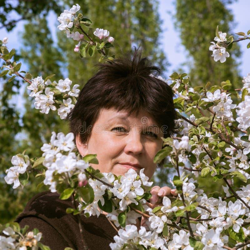 Portret van rijpe vrouw onder appelboom royalty-vrije stock foto