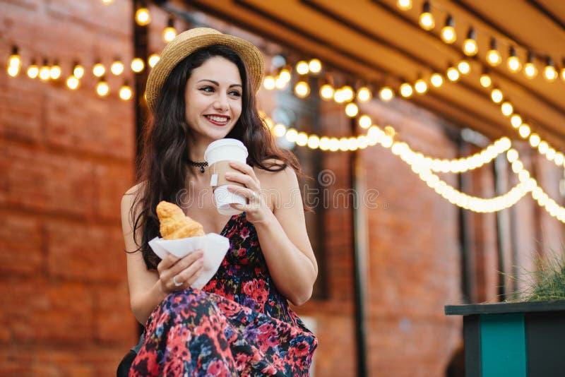 Portret van rustgevende vrouw met donker haar, glanzende ogen en goed-gevormde lippen die hoed en kleding dragen, die diner, croi royalty-vrije stock foto's