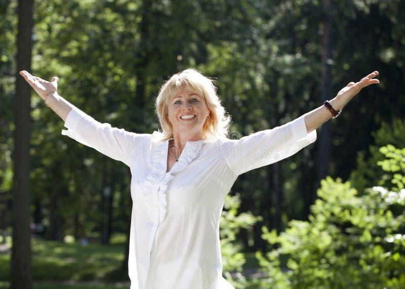 Portret van rustige rijpe vrouw in het de zomerpark stock fotografie