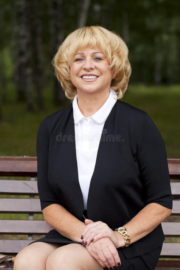 Portret van rustige rijpe vrouw in het de zomerpark stock afbeeldingen