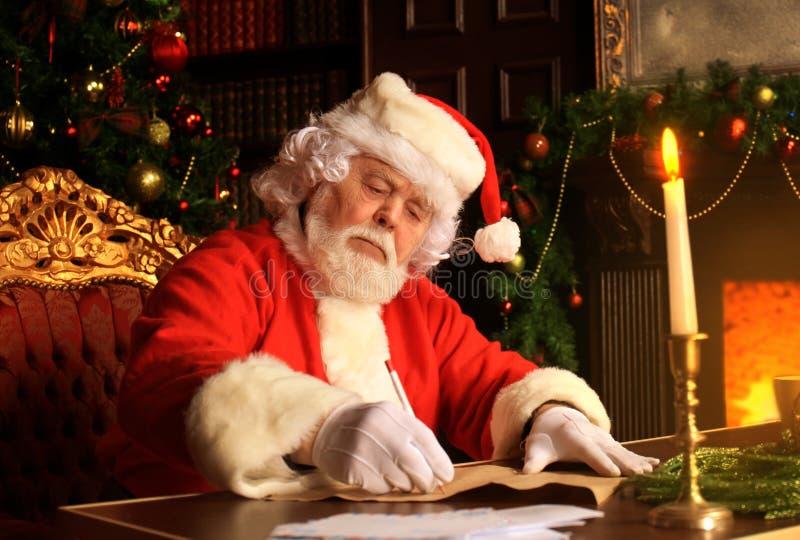 Portret van Santa Claus die Kerstmisbrieven beantwoorden royalty-vrije stock afbeeldingen