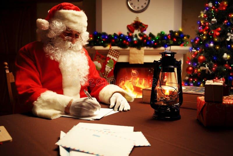Portret van Santa Claus die Kerstmisbrieven beantwoorden royalty-vrije stock foto's