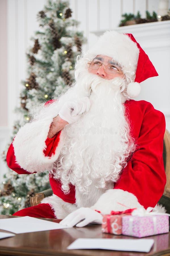 Portret van Santa Claus die Kerstmisbrieven beantwoorden stock afbeeldingen