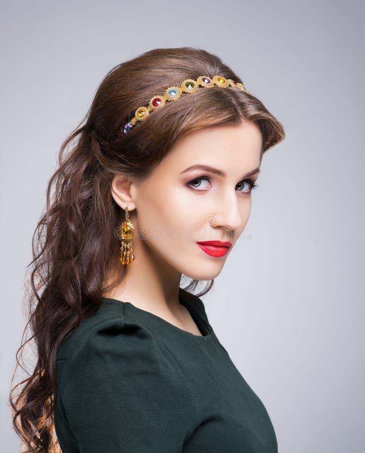 Portret van schitterend brunette die luxe gouden kroon en oorringen dragen royalty-vrije stock fotografie