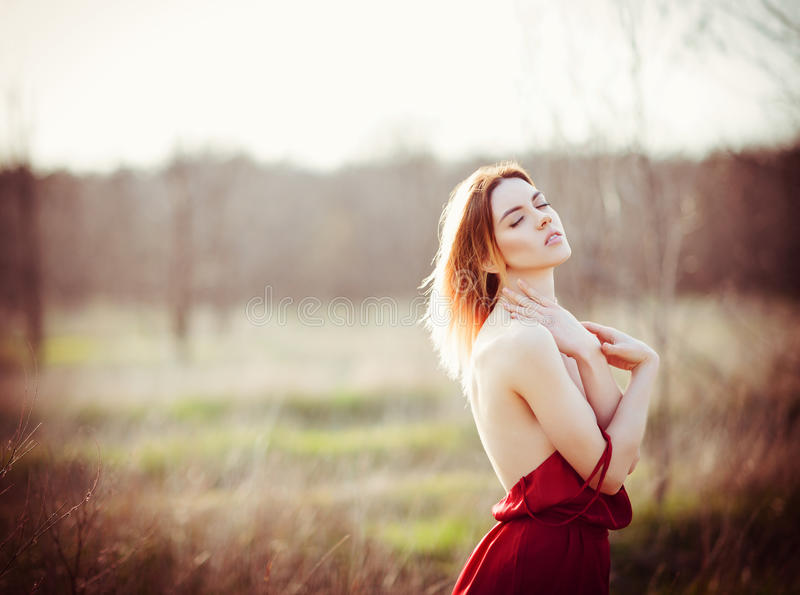 Portret van schitterende jonge vrouw die rode kleding op het gebied dragen bij zonsondergang royalty-vrije stock foto