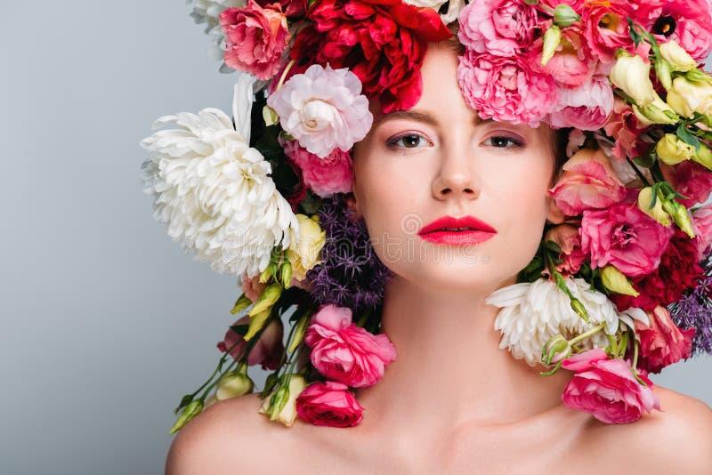 portret van schitterende naakte vrouw die met mooie bloemen op hoofd camera bekijken stock afbeeldingen