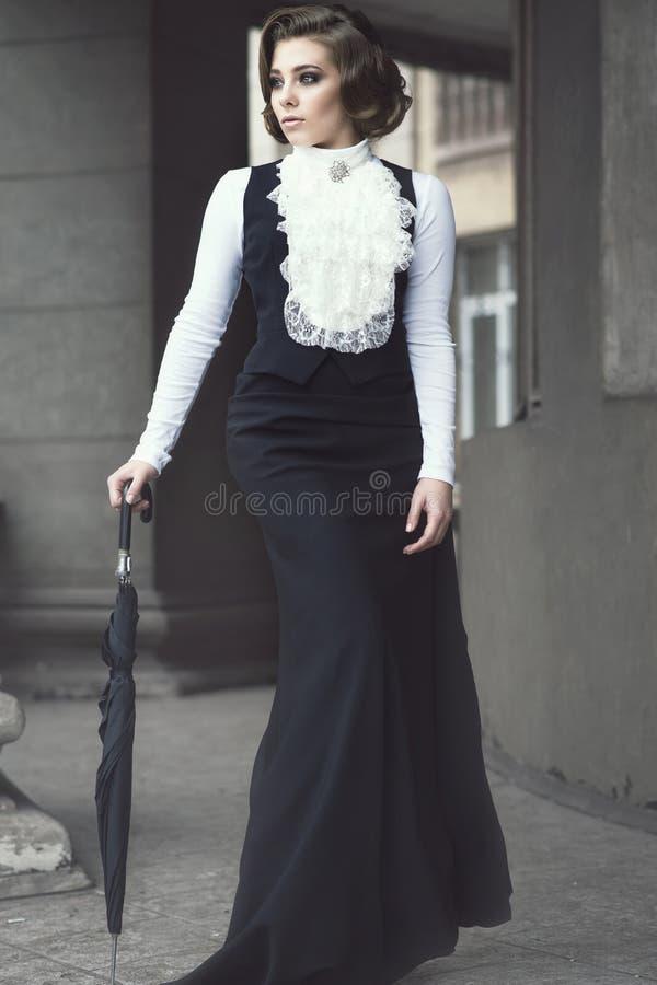 Portret van schitterende vrouw met elegant Victoriaans kapsel die ouderwetse toga dragen die onder de pijlers lopen stock foto
