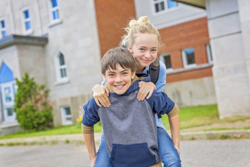 Portret van school 10 jaar jongens en meisje die pret hebben buiten stock afbeeldingen