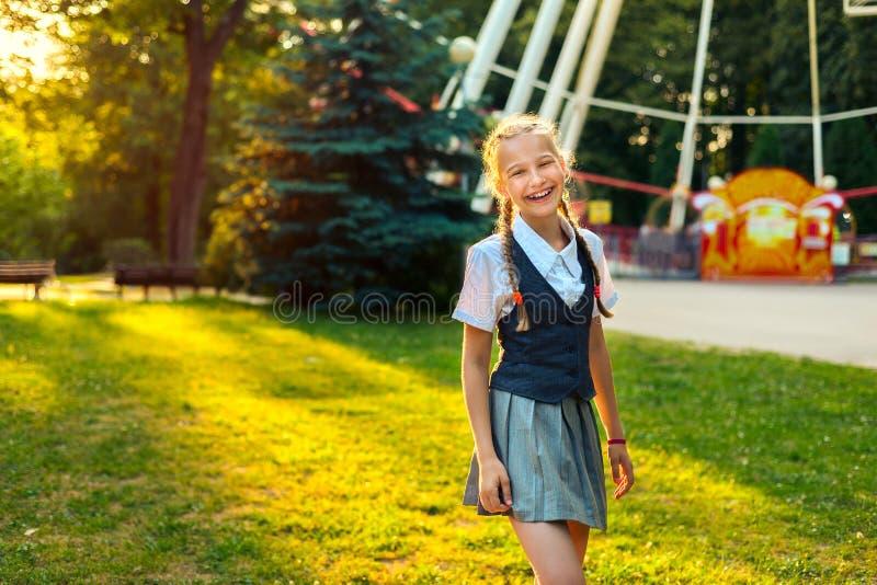Portret van schoolmeisje in zich het eenvormige lachen en het verheugen in de zomer in park royalty-vrije stock afbeeldingen