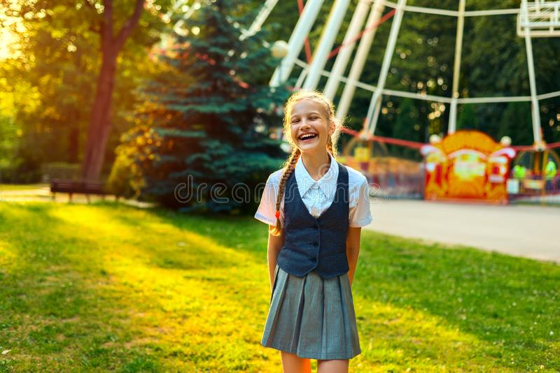 Portret van schoolmeisje in zich het eenvormige lachen en het verheugen in de zomer in park stock afbeelding