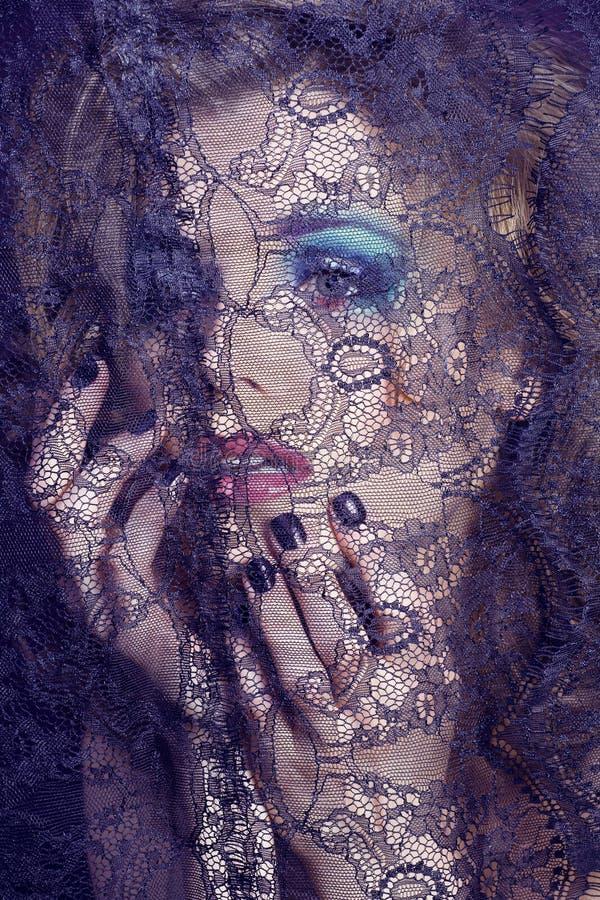 Portret van schoonheids jonge vrouw door kant dichte omhooggaande geheimzinnigheid mak stock fotografie