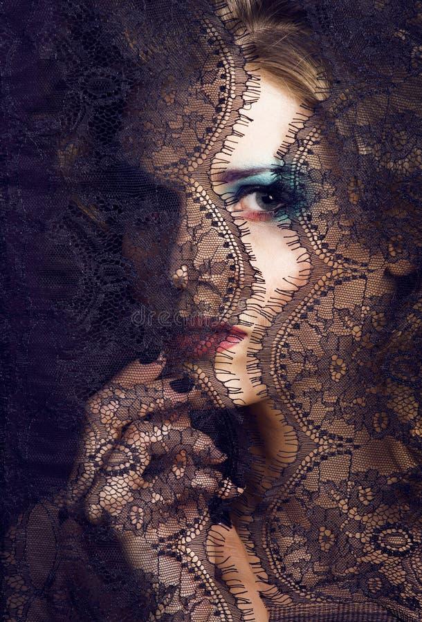 Portret van schoonheids jonge vrouw door kant dichte omhooggaande geheimzinnigheid mak royalty-vrije stock foto's