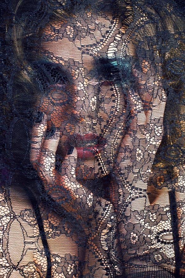 Portret van schoonheids jonge vrouw door kant dichte omhooggaande geheimzinnigheid mak royalty-vrije stock foto