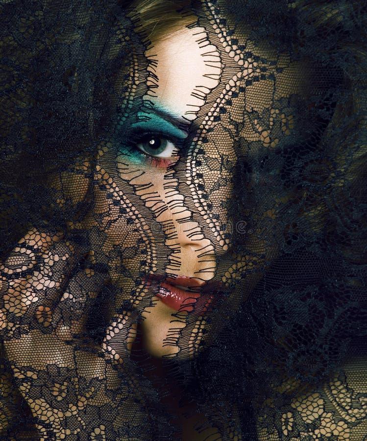 Portret van schoonheids jonge vrouw door kant dichte omhooggaande geheimzinnigheid mak royalty-vrije stock afbeeldingen