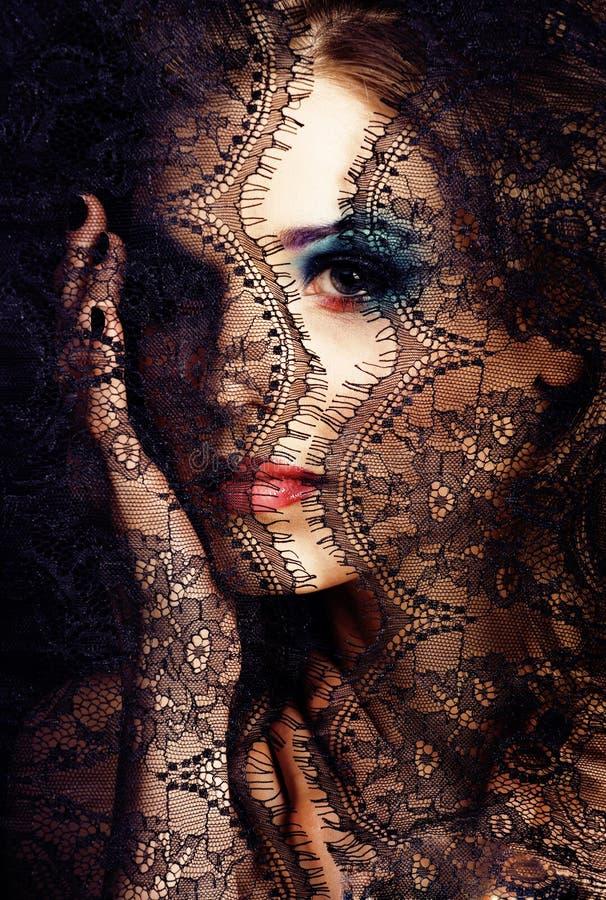 Portret van schoonheids jonge vrouw door kant dichte omhooggaande geheimzinnigheid mak royalty-vrije stock fotografie