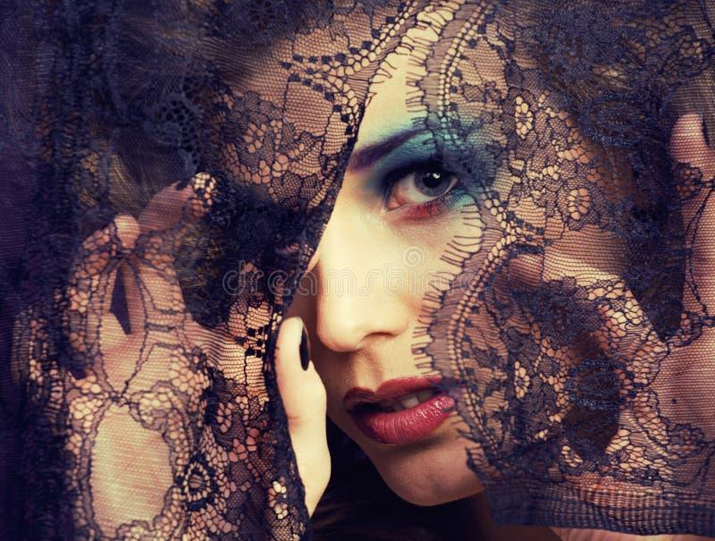Portret van schoonheids jonge vrouw door kant dichte omhooggaande geheimzinnigheid make-up stock foto