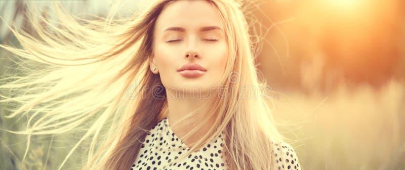 Portret van schoonheidsmeisje met fladderend wit haar die van aard in openlucht genieten Vliegend blondehaar op de wind Mooie Jon royalty-vrije stock afbeeldingen