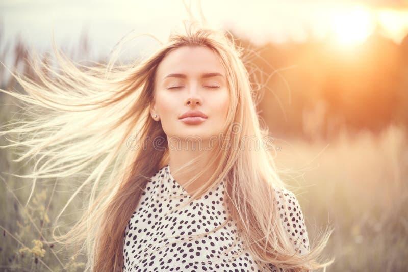 Portret van schoonheidsmeisje met fladderend wit haar die van aard in openlucht genieten Vliegend blondehaar op de wind Mooie Jon royalty-vrije stock foto's