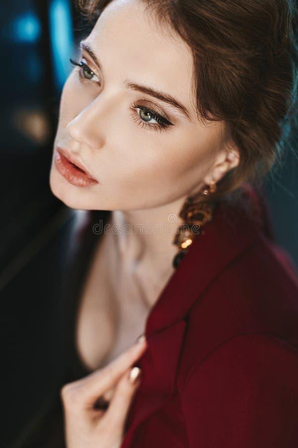 Portret van sensueel, modieus en mooi donkerbruin modelmeisje met heldere professionele make-up en met oorringen, in rode jacke royalty-vrije stock afbeelding