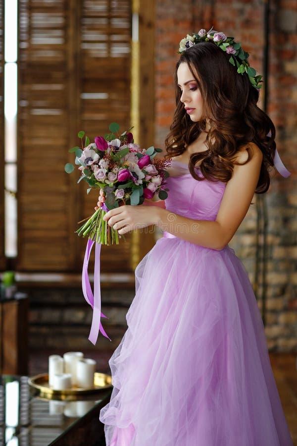 Portret van sensueel mooi donkerbruin meisje in purper kleding, kroon en boeket van bloemen schoonheid Witte achtergrond royalty-vrije stock afbeelding