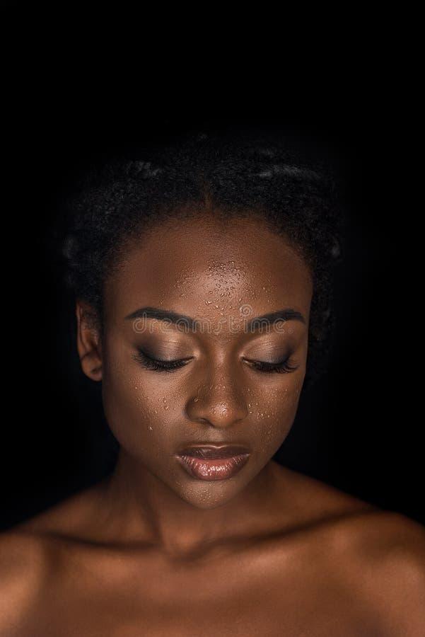 portret van sensuele jonge Afrikaanse Amerikaanse vrouw met waterdalingen bij gezicht het stellen met gesloten ogen royalty-vrije stock foto's