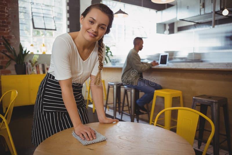 Portret van serveerster schoonmakende lijst stock foto's