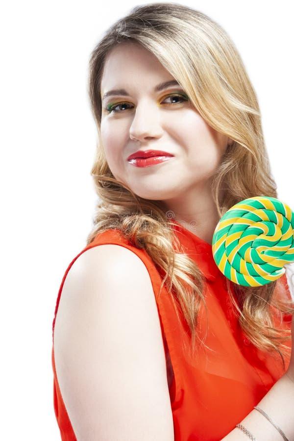 Portret van Sexy Alluring Caucasian Blond Girl Eating Round Lollipop op de stok nieuwsgierig Posing in Studio Tegen White stock afbeelding