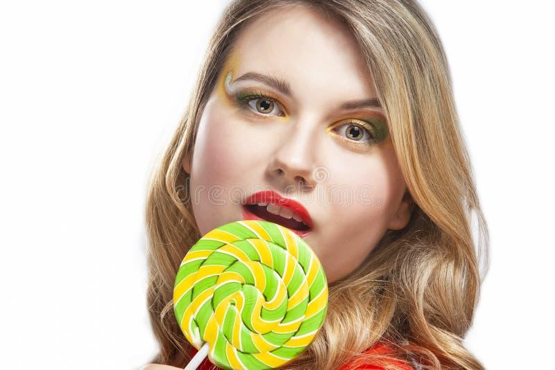 Portret van Sexy Alluring Caucasian Blond Girl Eating Round Lollipop op de stok Posing in Studio Tegen White stock fotografie