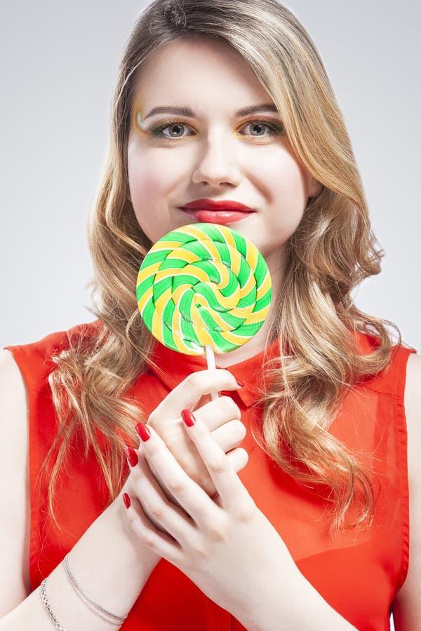Portret van Sexy Alluring Caucasian Blond Girl Eating Round Lollipop op de stok Posing in Studio Tegen White royalty-vrije stock fotografie