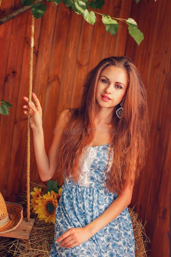 Portret van sexy jonge vrouwenzitting op het hooi stock foto's
