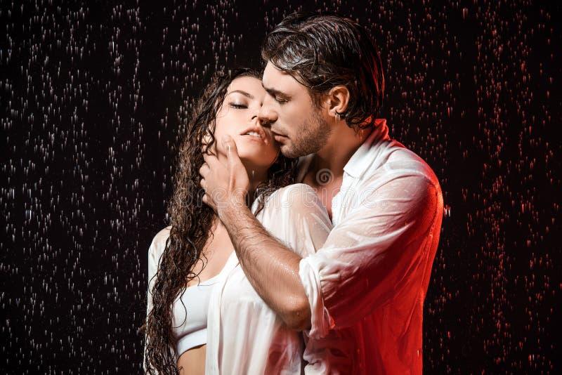 portret van sexy paar in witte overhemden die zich onder regen bevinden stock foto's