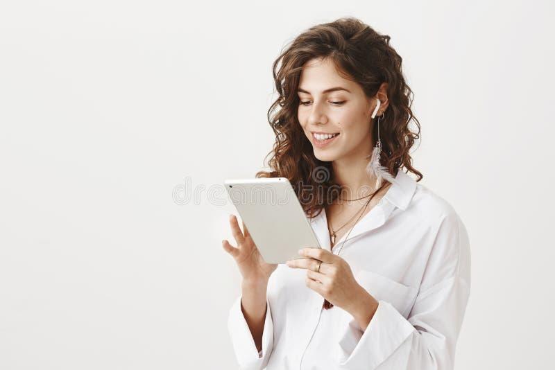 Portret van sexy zekere Kaukasische vrouw die met modieus kapsel in tablet met het brede glimlach en uitdrukken doorbladeren stock afbeeldingen