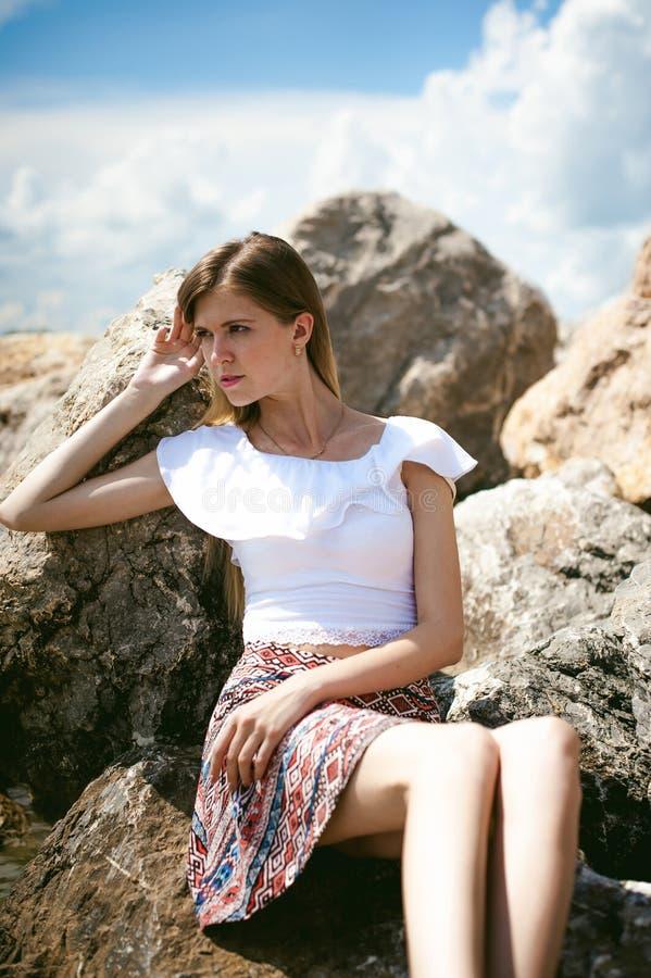 Portret van slanke jonge vrouw op stenen dichtbij het overzees stock foto's
