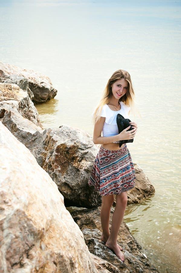 Portret van slanke jonge vrouw op stenen dichtbij het overzees stock afbeelding