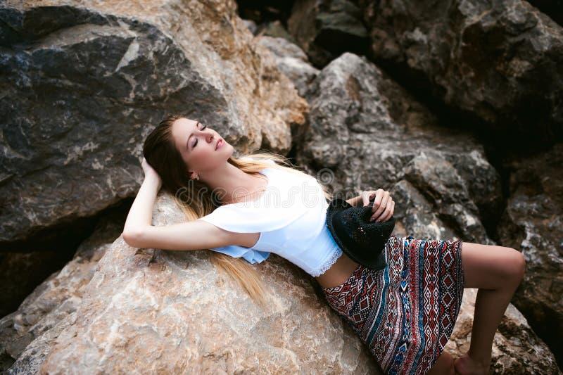 Portret van slanke jonge vrouw op stenen dichtbij het overzees royalty-vrije stock fotografie