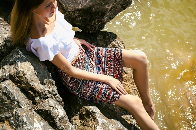 Portret van slanke jonge vrouw op stenen dichtbij het overzees royalty-vrije stock afbeelding