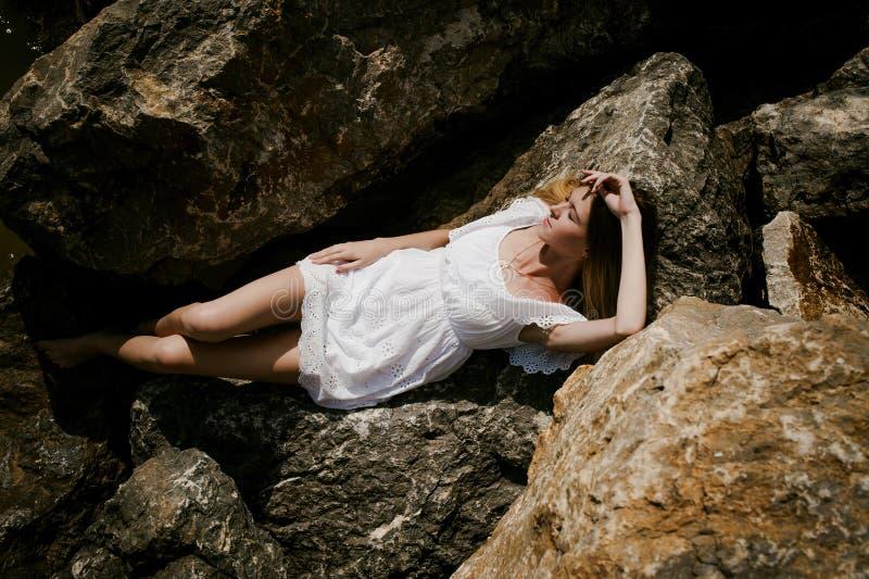 Portret van slanke jonge vrouw op stenen dichtbij het overzees royalty-vrije stock foto's