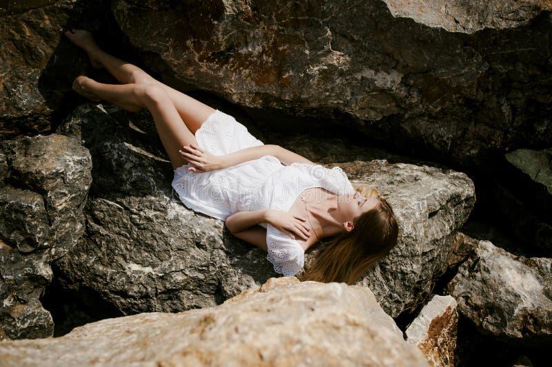 Portret van slanke jonge vrouw op stenen dichtbij het overzees stock foto