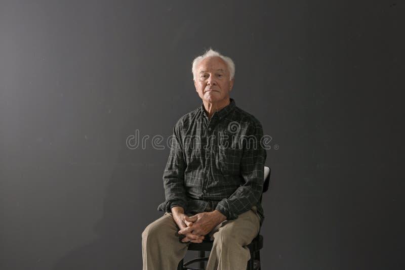 Portret van slechte bejaardezitting op stoel royalty-vrije stock afbeelding