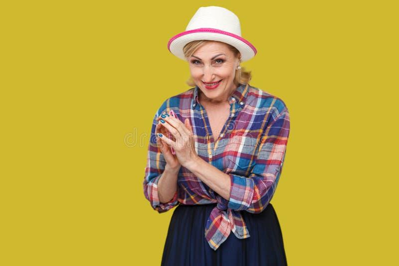 Portret van sluwe moderne modieuze rijpe vrouw in toevallige stijl met hoed en oogglazen die zich in sluw gebaar bevinden en beki stock fotografie