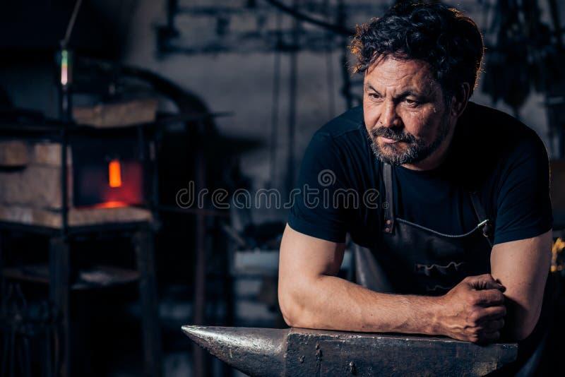 Portret van smid het voorbereidingen treffen om metaal aan het aambeeld te werken stock foto