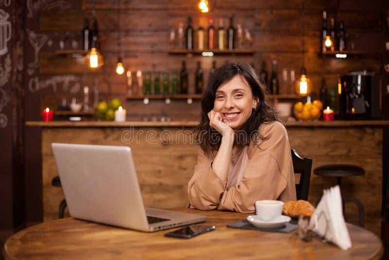 Portret van smillig jonge vrouw in een koffiewinkel met moderne computer dichtbij haar stock afbeeldingen