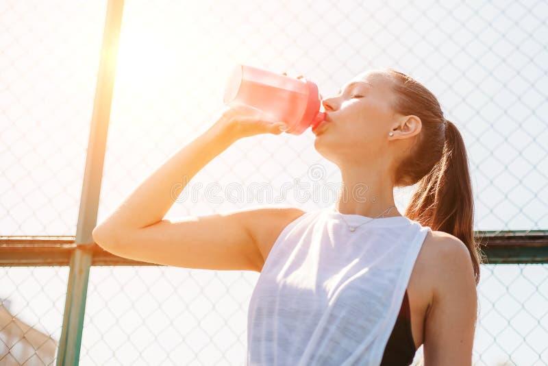 Portret van sportieve jonge sexy vrouw die koel water van fles op de zomersportterrein drinken Gezond levensstijlconcept royalty-vrije stock foto's